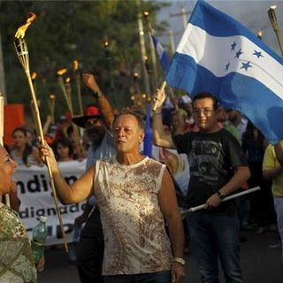 People take part in a march to demand the resignation of Honduras' President